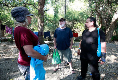 Dawn Redwood, a homeless woman living along Coyote Creek, speaks with Steve Chehy and Robert Aguirre (l-r) of  CHAM Ministries during a visit Thursday afternoon, June 30, 2016, in San Jose, Calif. (Karl Mondon/Bay Area News Group)