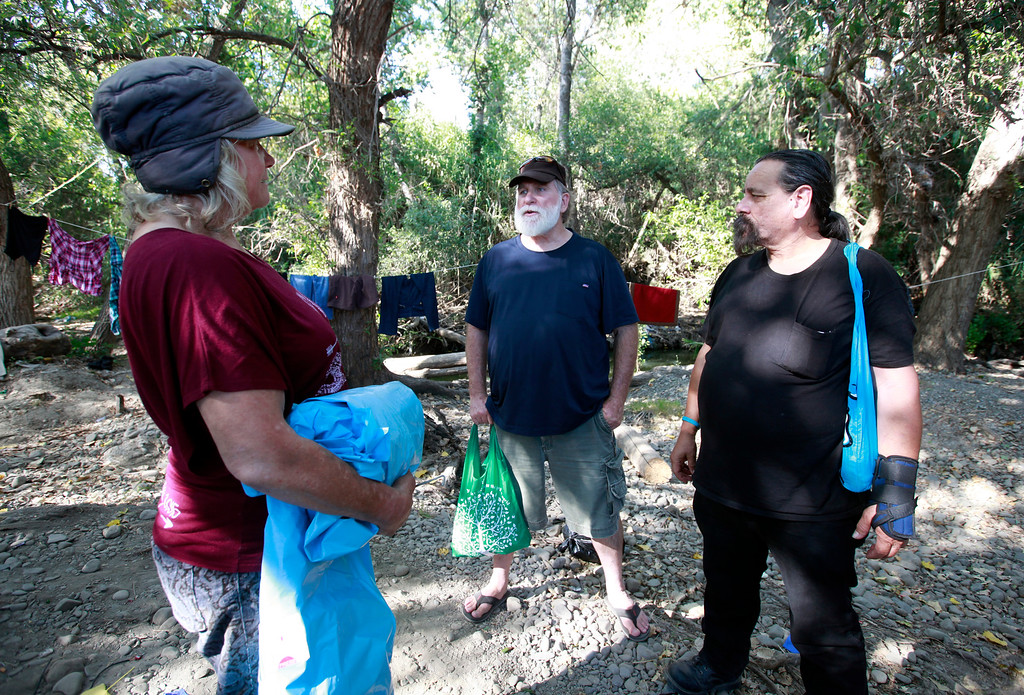 . Dawn Redwood, a homeless woman living along Coyote Creek, speaks with Steve Chehy and Robert Aguirre (l-r) of  CHAM Ministries during a visit Thursday afternoon, June 30, 2016, in San Jose, Calif. (Karl Mondon/Bay Area News Group)