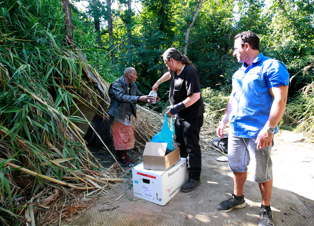 . Robert Aguirre offers fresh water to a homeless man living along Coyote Creek in San Jose, Calif., Thursday afternoon, June 30, 2016. Longtime homeless advocate Aguirre, visited the camp with Pastor Scott Wagers (right) of CHAM Ministry. (Karl Mondon/Bay Area News Group)