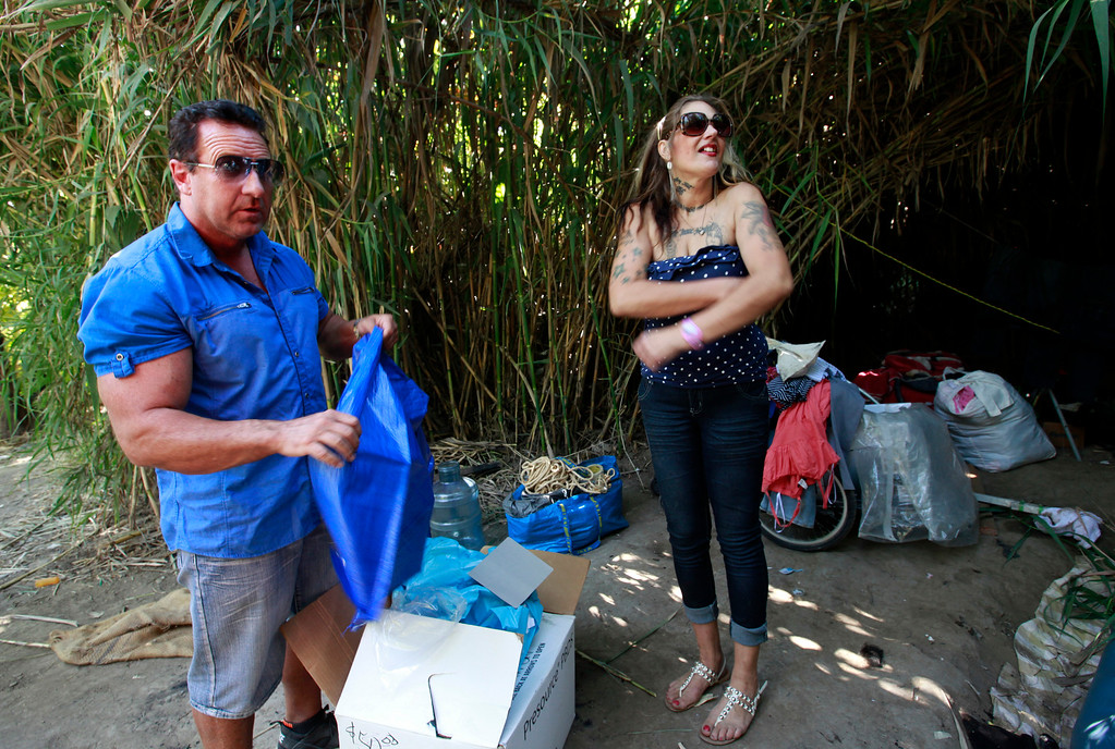 . Pastor Scott Wagers offers a free tarp to a homeless woman named Jennifer living at a Coyote Creek homeless camp in San Jose, Calif., Thursday afternoon, June 30, 2016. Wagers started CHAMP Ministry as a way to bring homeless services to people where they live. (Karl Mondon/Bay Area News Group)