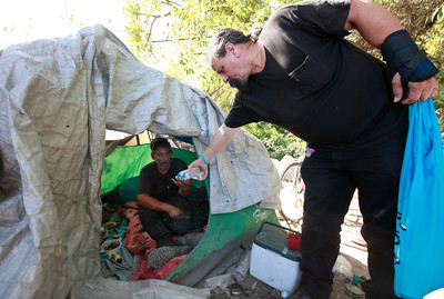 Homeless advocate Robert Aguirre offers fresh water to James Marc Turner at his camp along Coyote Creek in San Jose, Calif., Thursday afternoon, June 30, 2016. Turner is an 18 year veteran of living along the creek. (Karl Mondon/Bay Area News Group)