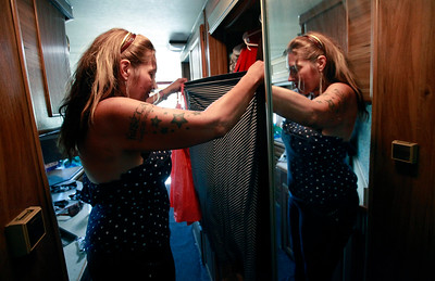 A homeless woman named Jennifer looks through the free clothing carried aboard Pastor Scott Wagers' CHAM Ministries mobile home, during a stop at a homeless camp along Coyote Creek in San Jose, Calif., Thursday afternoon, June 30, 2016. (Karl Mondon/Bay Area News Group)