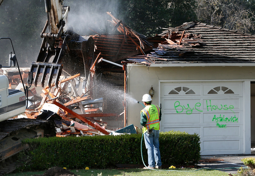 . Crews demolish James Bergeron\'s home in Menlo Park, Calif.,  Thursday afternoon, Feb. 27, 2014. The family found it more cost-effective to build a new house on that lot than to remodel the 67-year-old, slab foundation structure. (Karl Mondon/Bay Area News Group)