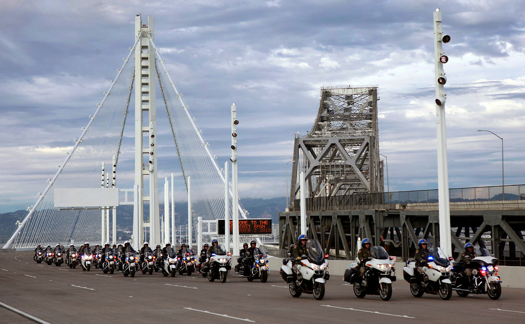 . A procession of California Highway Patrol motorcycle officers leads the first wave of vehicles over the new Bay Bridge after a chain-cutting bridge-opening ceremony Monday afternoon, Sept. 2, 2013 between Oakland and San Francisco, Calif. After 24 years of waiting, the Bay Area finally has its new bridge.   (Karl Mondon/Bay Area News Group)