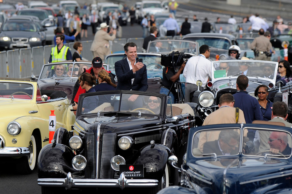. Lt. Governor Gavin Newsom records the scene as people gather into classic automobiles before crossing the new eastern span of the Bay Bridge in Oakland, Calif., on Monday, Sept. 2, 2013. The new 2.2 mile replacement eastern span with its skyward and iconic white tower and cables, is the world\'s largest self-anchored suspension span and California\'s most expensive infrastructure project to date. (Susan Tripp Pollard/Bay Area News Group)