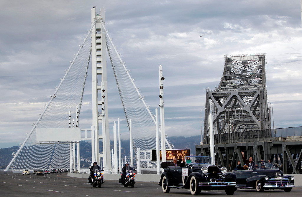 . Mayors Edwin Lee, of San Francisco, and Jean Quan, of Oakland, ride two vintage vehicles across the new Bay Bridge span after a chain-cutting ceremony Monday afternoon Sept. 2, 2013 in Oakland, Calif. After 24 years of waiting, the Bay Area finally has its new bridge.  (Karl Mondon/Bay Area News Group)