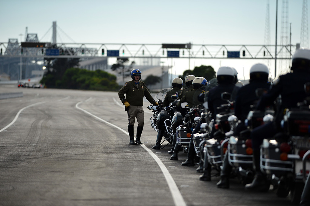 . Motorcycle police officers line up to escort a ceremonial procession onto the Bay Bridge following a chain-cutting ceremony to celebrate the completion of the new Bay Bridge in Oakland, Calif., on Monday, Sept. 2, 2013. (Kristopher Skinner/Bay Area News Group)