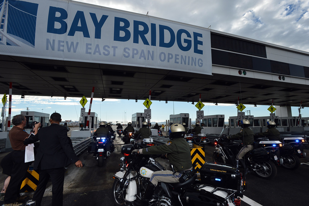 . Motorcycle police officers roll through the Bay Bridge toll plaza following a chain-cutting ceremony to celebrate the completion of the new Bay Bridge in Oakland, Calif., on Monday, Sept. 2, 2013. (Kristopher Skinner/Bay Area News Group)