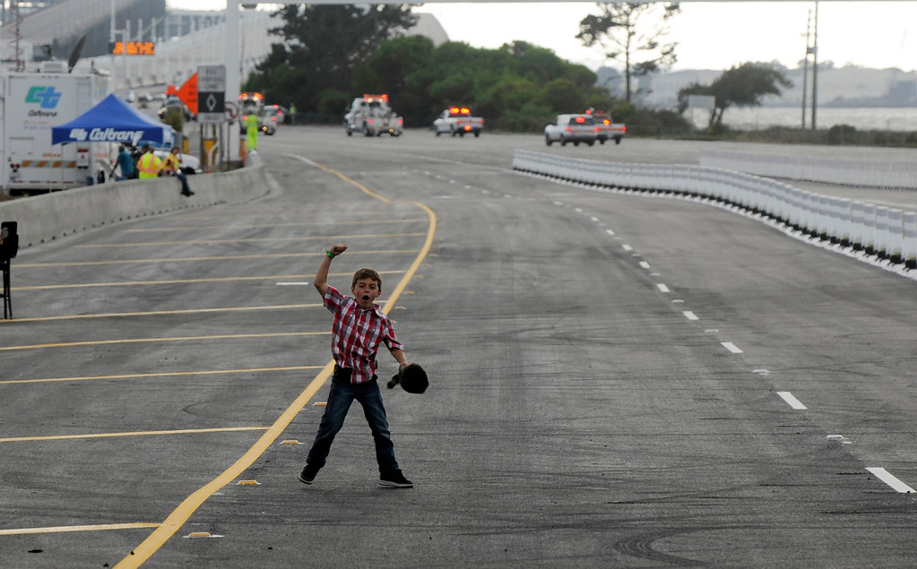 . A young boy jumps for joy in the car pool lane as vehicles travel west onto the BayBridge in Oakland, Calif., on Monday, Sept. 2, 2013. The new 2.2 mile replacement eastern span with its skyward and iconic white tower and cables, is the world\'s largest self-anchored suspension span and California\'s most expensive infrastructure project to date. (Susan Tripp Pollard/Bay Area News Group)