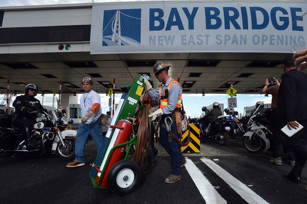 . Workers remove a cutting torch from the Bay Bridge toll plaza following a chain-cutting ceremony to celebrate the completion of the new Bay Bridge in Oakland, Calif., on Monday, Sept. 2, 2013. (Kristopher Skinner/Bay Area News Group)