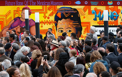 A painting of the late Peter Rodriguez, founder of the Mexican Museum, looks out over a gathering of people at the dedication ceremony for the museum's new site on Mission Street across from the Yerba Buena Gardens in San Francisco, Calif., Tuesday morning, July 19, 2016. The museum will reside in the first four floors of a 510-foot residential tower to be constructed behind the mural. (Karl Mondon/Bay Area News Group)