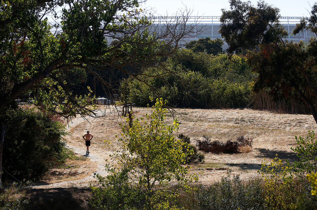 . James Vera of Santa Clara walks through the Ulistac Natural Area, with the future stadium for the San Francisco 49ers being built in the background, on his way to a jog in Santa Clara, Calif. on Thursday, Sept. 19, 2013.  The 49ers and the city of Santa Clara are proposing to develop part of a 40-acre natural open space into soccer fields to make way for extra parking next to the new stadium.  Vera thinks it\'s a good idea move the soccer fields.  (Nhat V. Meyer/Bay Area News Group)
