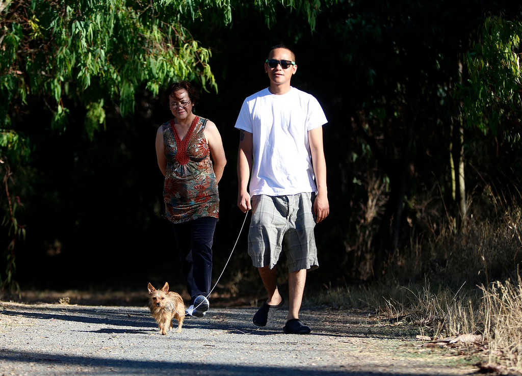 . Joselito Natnat, right, walks his dog Snicky, along with his mom Olivia Natnat, all from Santa Clara, at Ulistac Natural Area in Santa Clara, Calif. on Thursday, Sept. 19, 2013.  The 49ers and the city of Santa Clara are proposing to develop part of a 40-acre natural open space into soccer fields to make way for extra parking next to the new stadium.  Joselito was sad to hear that they might replace parts of the area with a soccer field, he likes to have the natural space to close by.  (Nhat V. Meyer/Bay Area News Group)