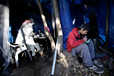 """Michelle Allmon, 43, and Bobby Tovar, 23, try to stay warm during a cold morning in an  encampment known as """"The Jungle"""" near Coyote Creek in San Jose, Calif. on Tuesday, Dec. 10, 2013. A team from the Valley Homeless Healthcare Program paid a visit to their campsite to check on their medical needs. The program sponsored by Santa Clara County provides immediate medical care from a mobile medical unit. Outreach teams are also sent into the camps to provide medical services for those who have seldom sought medical care in the past.  (Gary Reyes/Bay Area News Group)"""