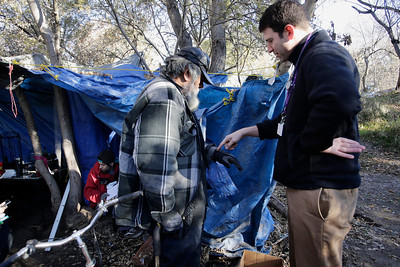 """Dr. Ari Kriegsman, right, talks to Chris Salazar about some hand pain he is experiencing during a weekly visit by doctors of the Valley Homeless Healthcare Program to an encampment known as """"The Jungle"""" near Coyote Creek in San Jose, Calif. on Tuesday, Dec. 10, 2013. The program sponsored by Santa Clara County provides immediate medical care from a mobile medical unit. Outreach teams are also sent into the camps to provide medical services for those who have seldom sought medical care in the past. (Gary Reyes/Bay Area News Group)"""