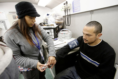 """Antonietta Scrofani takes the vital signs of Vicente Montes in a mobile medical unit at the site of a homeless encampment known as """"The Jungle"""" near Coyote Creek in San Jose, Calif. on Tuesday, Dec. 10, 2013. Scrofani is member of team from the Valley Homeless Healthcare Program sponsored by Santa Clara County that provides immediate medical care fro the homeless from a mobile medical unit. Outreach teams are also sent into the camps to provide medical services for those who have seldom sought medical care in the past.  Montes was recently released from prison and is homeless. He came to the mobile clinic to make sure he was in good health. (Gary Reyes/Bay Area News Group)"""