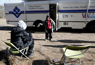 """Erasmo Torres, 53, and Michelle Allmon, 43, wait to see the doctors in an outdoor waiting room in front of the Valley Homeless Healthcare Program's mobile medical unit at an encampment known as """"The Jungle"""" near Coyote Creek in San Jose, Calif. on Tuesday, Dec. 10, 2013. The program sponsored by Santa Clara County provides immediate medical care from the mobile medical unit which comes to the site once a week. Outreach teams are also sent into the camps to provide medical services for those who have seldom sought medical care in the past.  (Gary Reyes/Bay Area News Group)"""