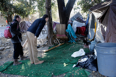 """Dr. Ari Kriegsman, right, and psychologist, Charles Preston, left, of the Valley Homeless Healthcare Program try to make contact with a resident in an encampment known as """"The Jungle"""" near Coyote Creek during a weekly visit to the tent city in San Jose, Calif. on Tuesday, Dec. 10, 2013. The program sponsored by Santa Clara County provides immediate medical care from a mobile medical unit. Outreach teams are also sent into the camps to provide medical services for those who have seldom sought medical care in the past.  (Gary Reyes/Bay Area News Group)"""