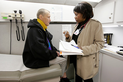 """Mercy Egbujor, nurse practitioner from the Valley Homeless Healthcare Program, prescribes medicine to Meredith Caballero, 64, during a visit by the mobile medical unit to the homeless encampment known as """"The Jungle"""" near Coyote Creek in San Jose, Calif. on Tuesday, Dec. 10, 2013. Caballero had been suffering from a lingering cough. The program sponsored by Santa Clara County provides immediate medical care from a mobile medical unit that comes to the encampment once a week. Outreach teams are also sent into the camps to provide medical services for those who have seldom sought medical care in the past.  (Gary Reyes/Bay Area News Group)"""