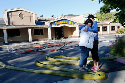 Mary Guercio, left, consoles employee, Danielle Dominguez, right, while viewing the damage from a three-alarm fire at Double D's Sports Grille in Los Gatos, Calif., on Monday, April 25, 2016. Guercio owns a small business down the street. (Gary Reyes/Bay Area News Group)