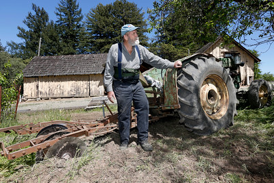 Robert Criswell, 71, stands with his 1949 tractor that he uses to create a fire break around his property at the Black Road Christmas Tree Farms in Los Gatos, Calif., on Thursday, April 16, 2015. The continued drought conditions has residents and businesses like Criswell's concerned as fire season comes earlier than normal.  (Gary Reyes/Bay Area News Group)