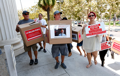Peter Ross, Joseph Soto-Hockenberry, and Maria Ruiz, left to right, deliver symbolic boxes of signed petitions calling for the impeachment of Santa Clara County Superior Court Judge Aaron Persky at the Old Courthouse in San Jose, Calif., on Monday, Aug. 1, 2016. Upset by the light jail sentence he gave former Stanford student Brock Turner for sexually assaulting an unconscious woman, the protesters submitted 1.2 million signatures in a petition to oust the judge. (Photo by Gary Reyes/Bay Area News Group)