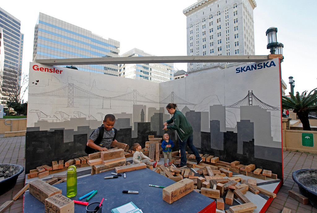 """. Seven year-old Joshua Henry from Oakland is busy creating a tower as Lindsay Gramana from San Francisco plays with her two kids in the \""""Block by Block\"""" installation  at Frank Ogawa Plaza in Oakland, Calif.,  on Friday, Feb. 5, 2016.  The non-profit Our City partnered with the City of Oakland to bring a Public Design Fair to Oakland promoting \""""play\"""", the theme of the three-day interactive fair. (Laura A. Oda/Bay Area News Group)"""