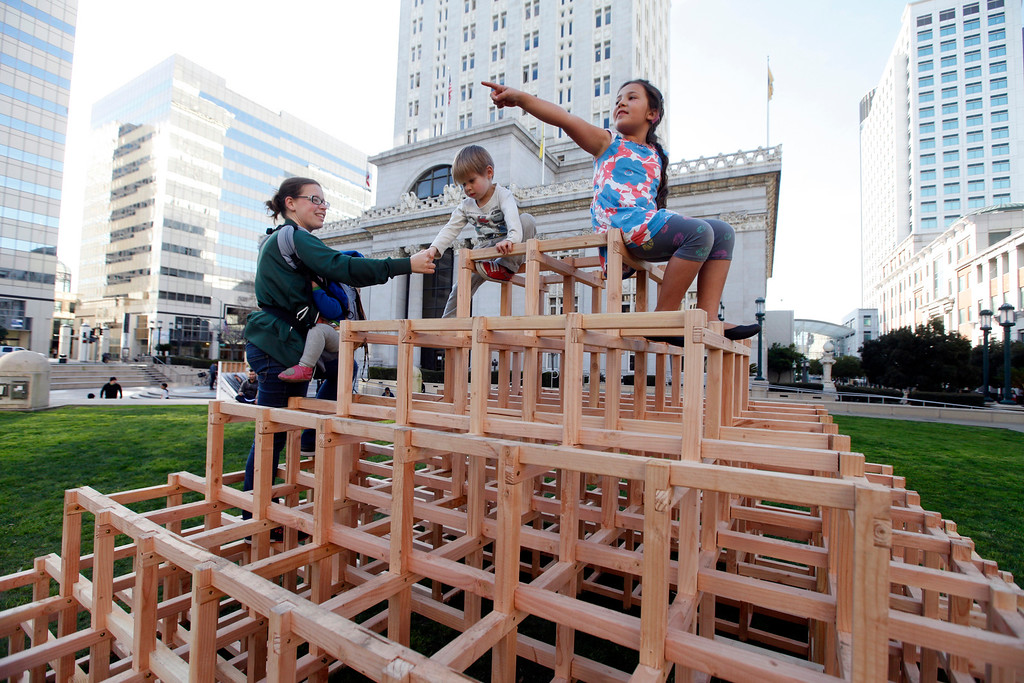 ". Lindsay Gramana from San Francisco helps her son Rex, 3, down from the ""Scaffoldia\"" installation as Monrovia Prinz, 7, from Oakland points to another attraction at Frank Ogawa Plaza in Oakland, Calif.,  on Friday, Feb. 5, 2016.  The non-profit Our City partnered with the City of Oakland to bring a Public Design Fair to Oakland promoting \""play\"", the theme of the three-day interactive fair. (Laura A. Oda/Bay Area News Group)"