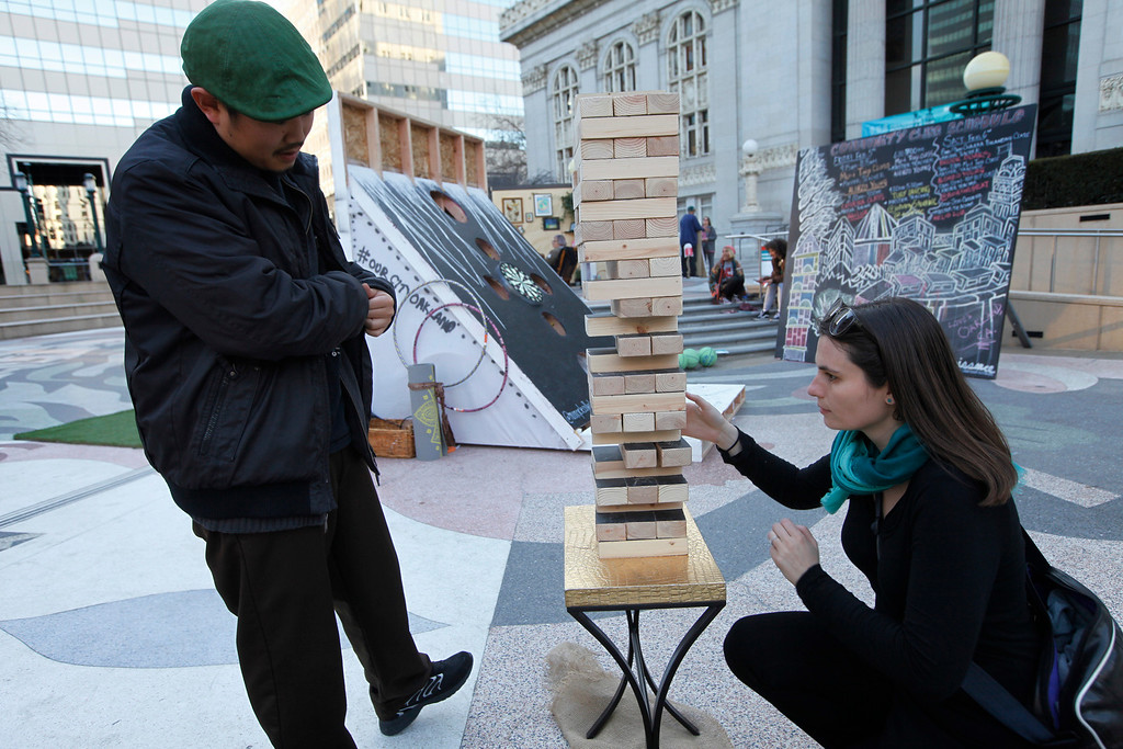 ". Ryan Castillo, from Oakland, left, and Judith Pierce, also from Oakland, play a large version of Jenga in the ""It\'s LIT\"" a multigenerational playground at Frank Ogawa Plaza in Oakland, Calif., on Friday, Feb. 5, 2016.  The non-profit Our City partnered with the City of Oakland to bring a Public Design Fair to Oakland promoting \""play\"", the theme of the three-day interactive fair. (Laura A. Oda/Bay Area News Group)"
