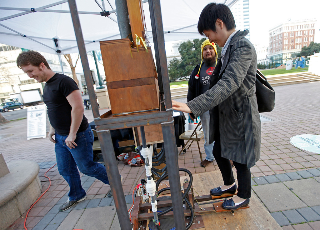 ". Stacy Suh from Oakland tries out the pipe organ powered by air pumps made by members of the Crucible at Frank Ogawa Plaza in Oakland, Calif.,  on Friday, Feb. 5, 2016.  The non-profit Our City partnered with the City of Oakland to bring a Public Design Fair to Oakland promoting ""play\"", the theme of the three-day interactive fair. (Laura A. Oda/Bay Area News Group)"