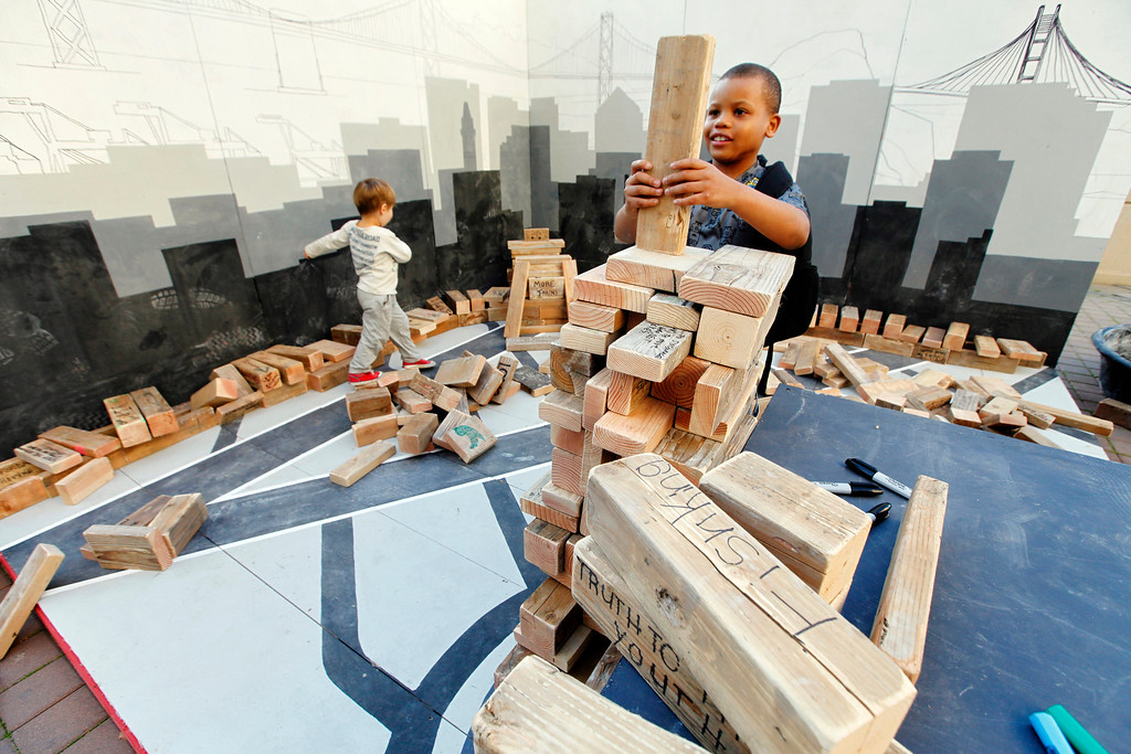 """. Joshua Henry, 7, puts the final block on his masterpiece building at the \""""Block by Block\"""" installation at Frank Ogawa Plaza in Oakland, Calif., on Friday, Feb. 5, 2016.  The non-profit Our City partnered with the City of Oakland to bring a Public Design Fair to Oakland promoting \""""play\"""", the theme of the three-day interactive fair. (Laura A. Oda/Bay Area News Group)"""