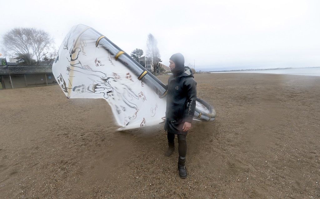 . J.T. Tran, of Alameda prepares his kite for kite boarding along the water at Crown Beach in Alameda, Calif., on Saturday, Feb. 8, 2014. There was intermittent rain and wind all day, but for kite boarders, the wind was a little light. (Dan Honda/Bay Area News Group)