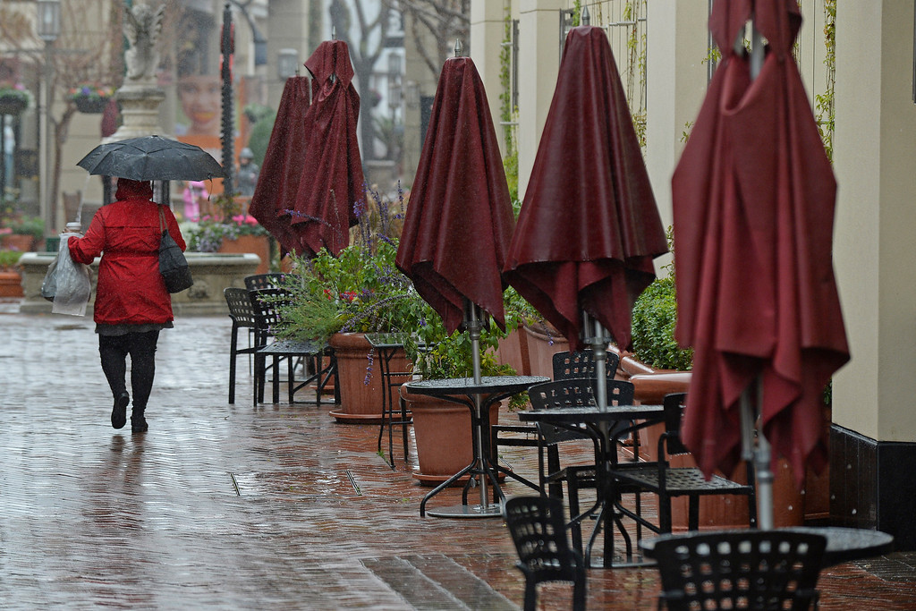 . A woman walks in the rain while shopping at Broadway Plaza in Walnut Creek, Calif., on Saturday, Feb. 8, 2014. (Jose Carlos Fajardo/Bay Area News Group)