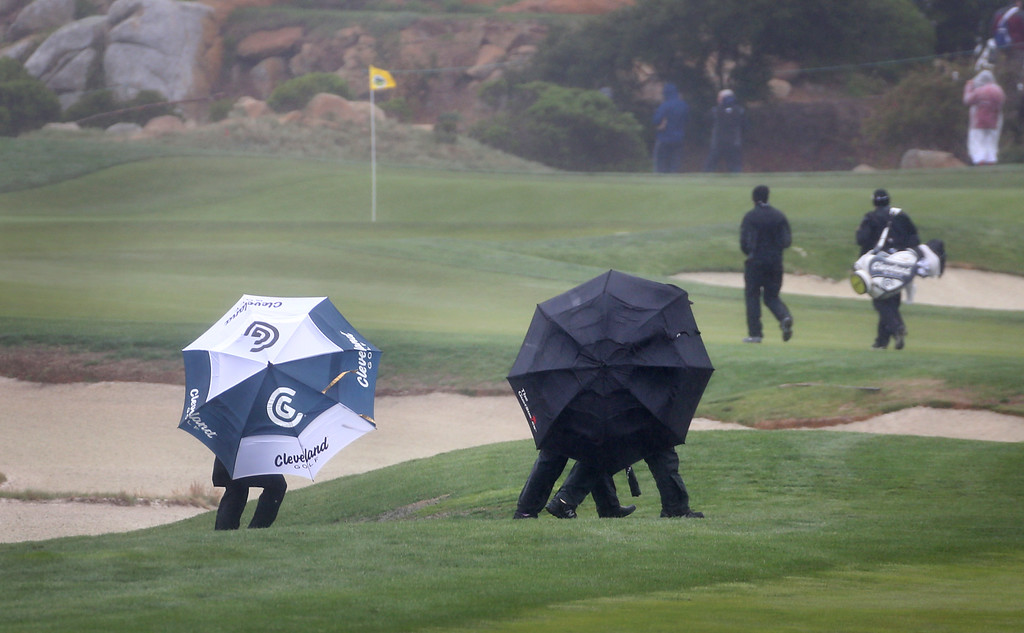 . Fans cross the fifth hole at Monterey Peninsula Country Club Shore Course just before play was suspended because of high winds during the third round of the annual Pebble Beach Pro-Am golf tournament in Pebble Beach Saturday, Feb. 8, 2014. (Patrick Tehan/Staff)