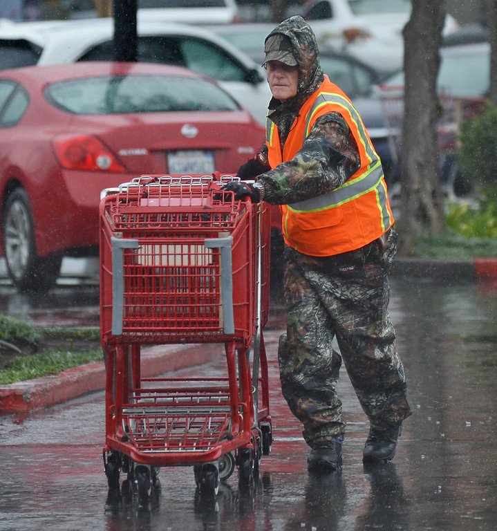 . John Lohnes, of Trader Joe\'s in Concord, braves the heavy rain to collect shopping carts in Concord, Calif., on Saturday, Feb. 8, 2014. (Dan Rosenstrauch/Bay Area News Group)