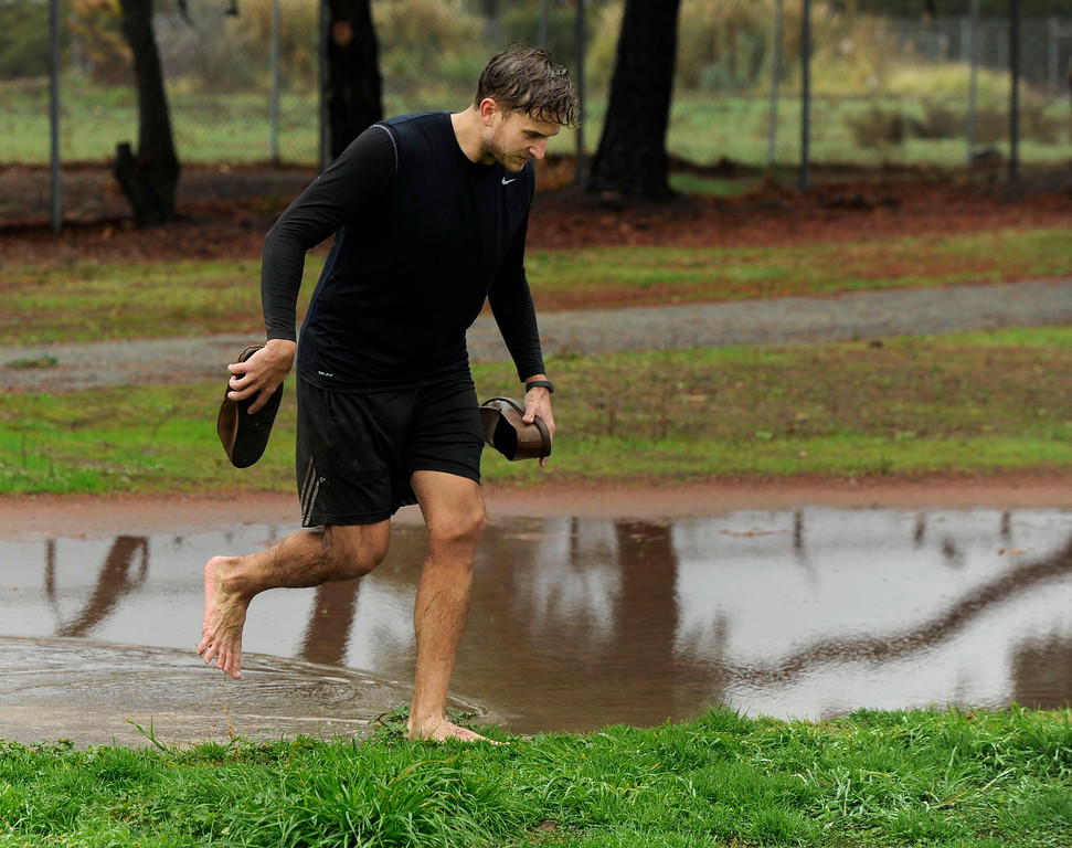 . At the end of his Ultimate Frisbee game, Aaron DeMers of Vallejo wades through a puddle to clean up a bit in Pleasant Hill, Calif., Sunday, Feb. 9, 2014. The wet weather did not bother the players who slipped and slid on the field during their game. (Susan Tripp Pollard/Bay Area News Group)