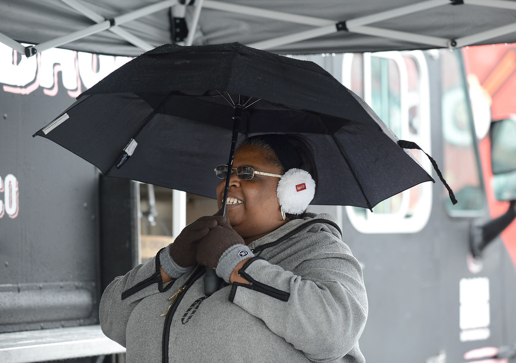 . Jackie Steward, of Oakland, braves the wind and cold to have lunch at a gathering of food trucks at the South Shore Center in Alameda, Calif., on Saturday, Feb. 8, 2014. There was intermittent rain and wind all day. (Dan Honda/Bay Area News Group)