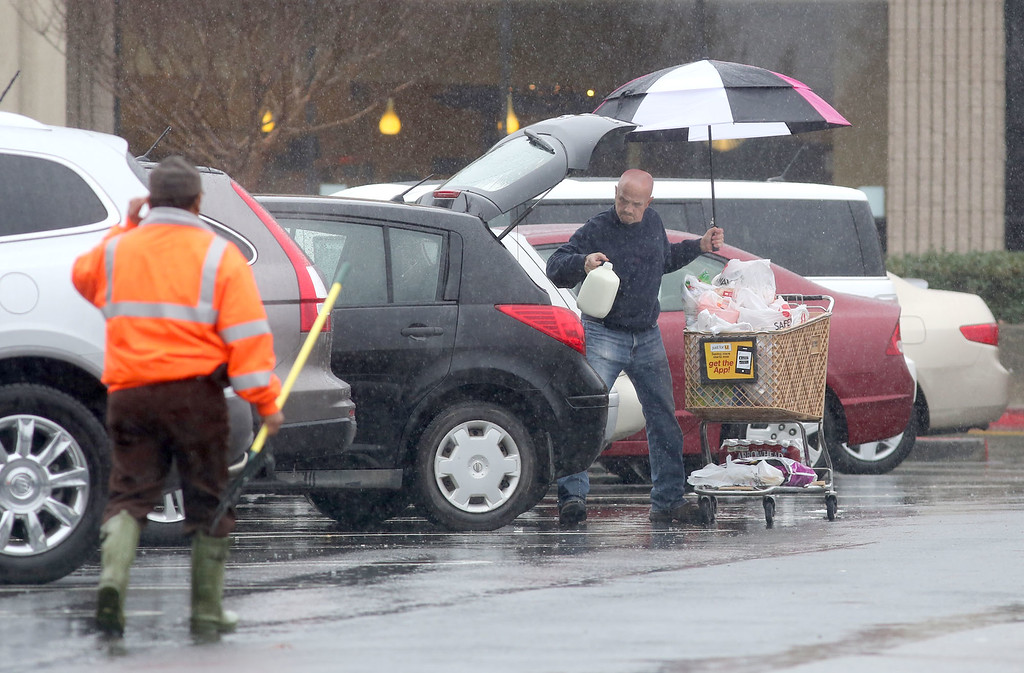 . A shopper loads groceries into his vehicle after shopping at Diablo Plaza center in San Ramon, Calif., on a rainy Sunday, Feb. 9, 2014. The workman on the left has just finished clearing debris from storm drains in the parking lot.  (Jim Stevens/Bay Area News Group)
