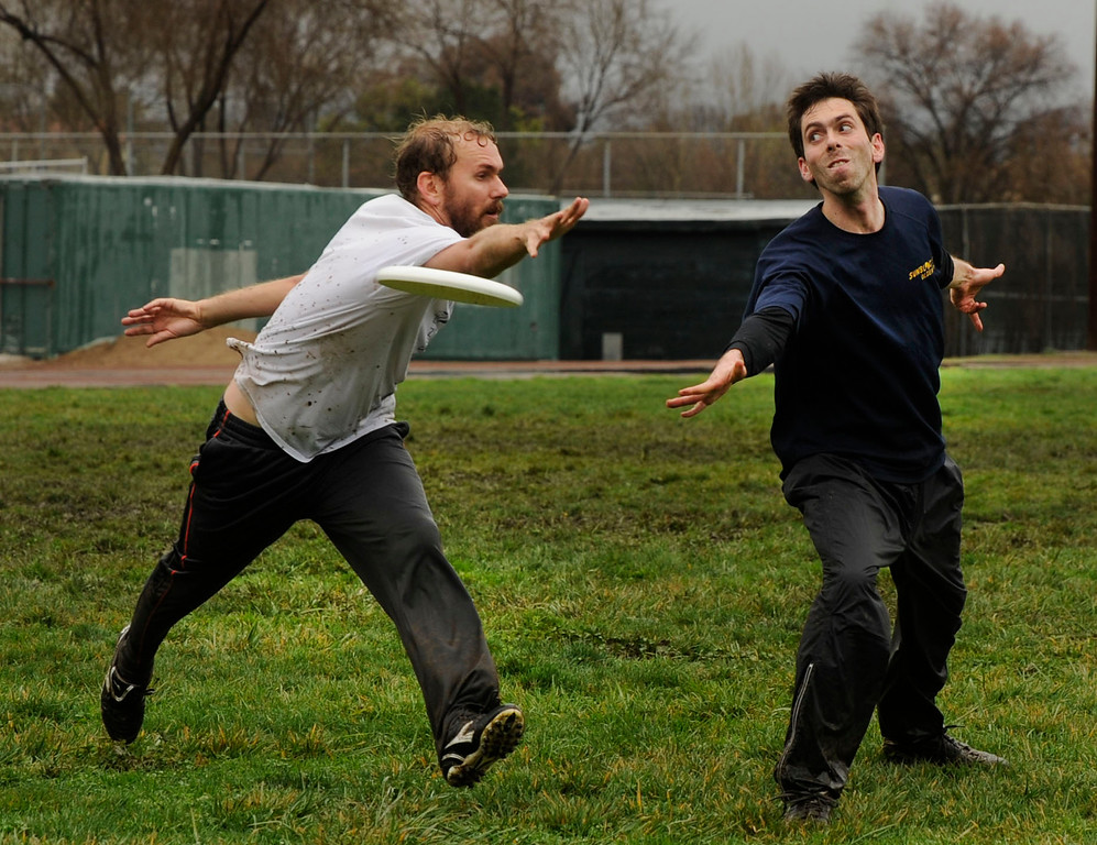 . Michael Starr, of Danville, left, playing for the white team tries to block a pass by Csaba Farks, of Pleasanton playing for the color shirts team during their Ultimate Frisbee game in Pleasant Hill, Calif., Sunday, Feb. 9, 2014. The wet weather did not bother the players who slipped and slid on the field and cleaned up in nearby puddles after their game. (Susan Tripp Pollard/Bay Area News Group)