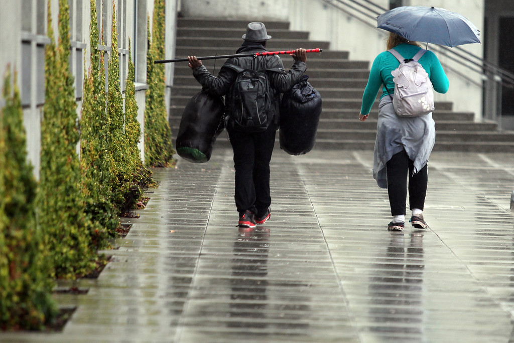 . Pedestrians walks past The Cathedral of Christ the Light in Oakland, Calif., as the rain continues falling on Saturday, Feb. 8, 2014. (Ray Chavez/Bay Area New Group)