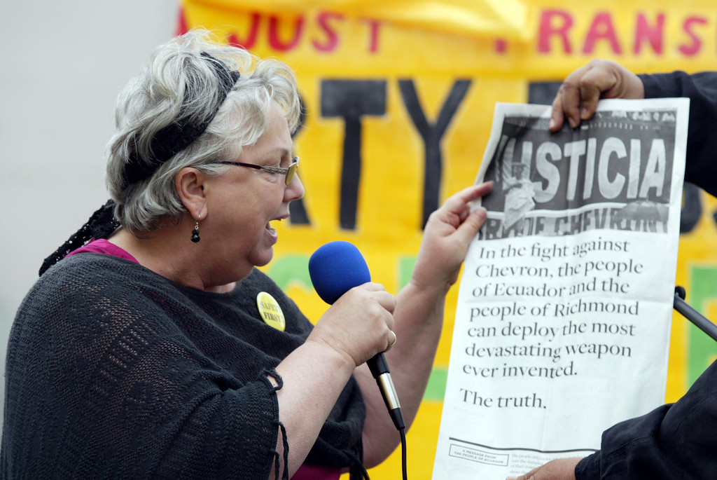 . Richmond Mayor Gayle McLaughlin reads a newspaper add against Chevron from the people of Ecuador during a rally at Richmond BART station in Richmond, Calif., on Saturday, Aug. 3, 2013. About 500 demonstrators took part in the rally followed by a march to the Chevron refinery. (Ray Chavez/Bay Area News Group)