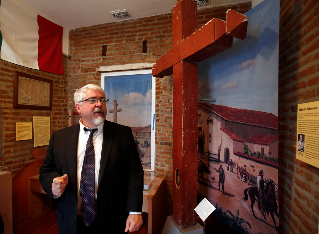 . Superior Court Judge Paul Bernal leads a tour through the Roberto Adobe and Sunol House Museum in San Jose, Calif., Monday, Aug. 22, 2016, stopping at a 1902-circa cross from nearby Mission Santa Clara. (Karl Mondon/Bay Area News Group)