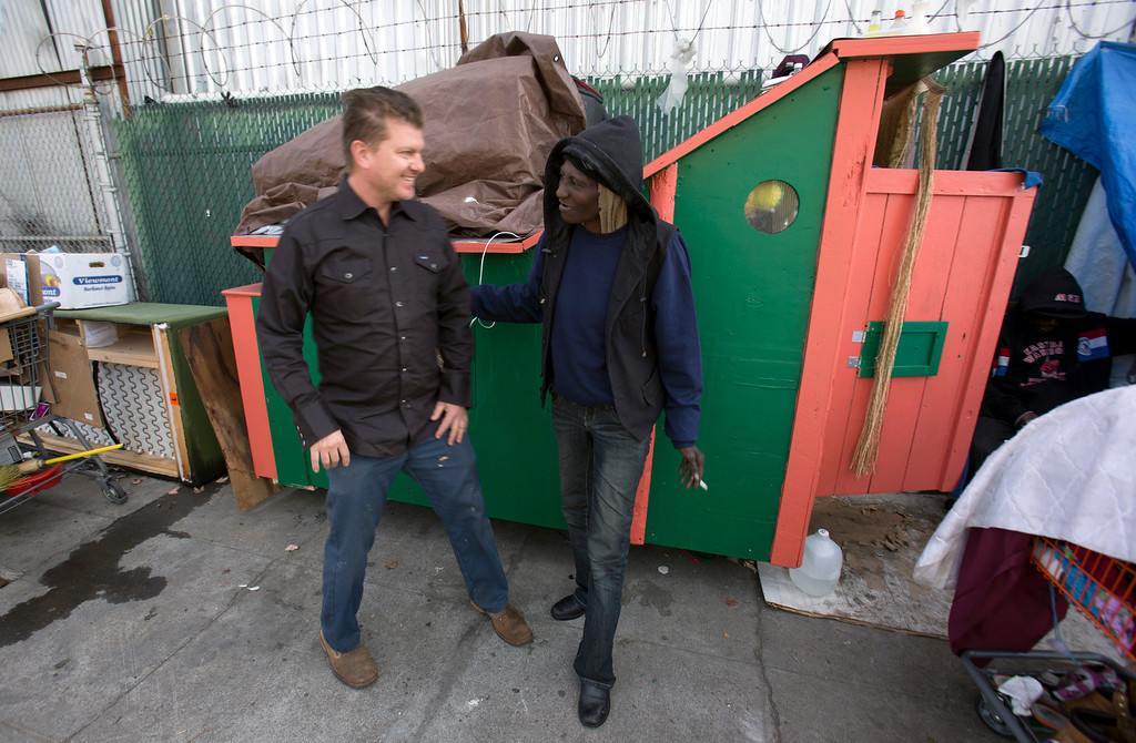 ". Greg Kloehn, who takes discarded trash and turns it into rolling shelters for homeless people in his west Oakland, Calif. neighborhood, greets ""Wonder,\"" a homeless woman who now lives in the shelter he built for her, Tuesday, Dec. 31, 2013. (D. Ross Cameron/Bay Area News Group)"