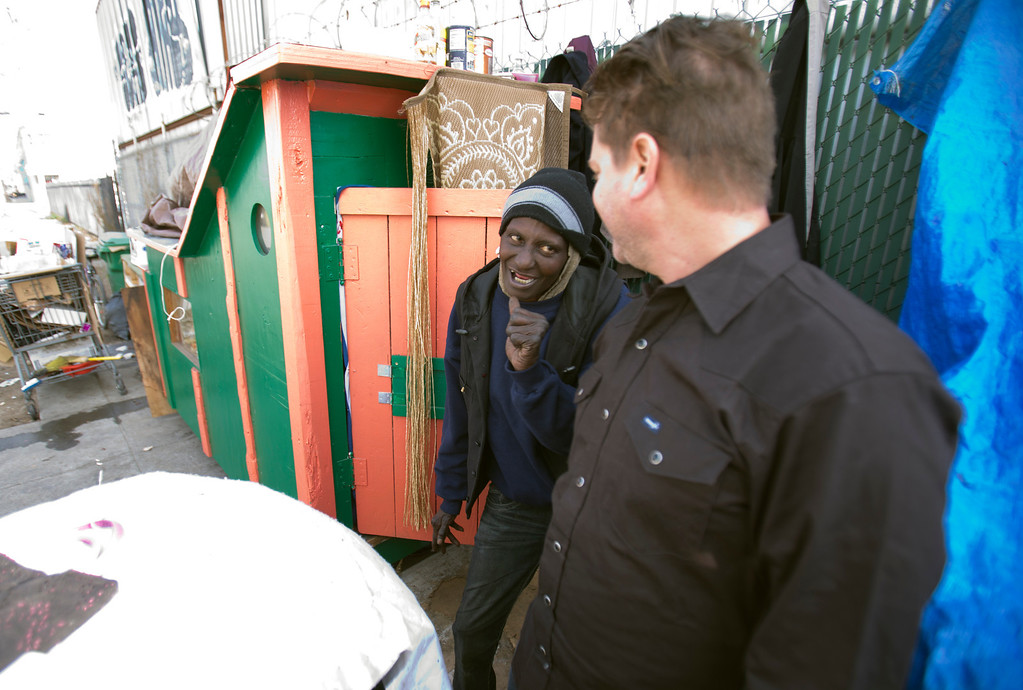 ". Greg Kloehn, right, who takes discarded trash and turns it into rolling shelters for homeless people in his west Oakland, Calif. neighborhood, greets ""Wonder,\"" a homeless woman who now lives in the shelter he built for her, Tuesday, Dec. 31, 2013. (D. Ross Cameron/Bay Area News Group)"