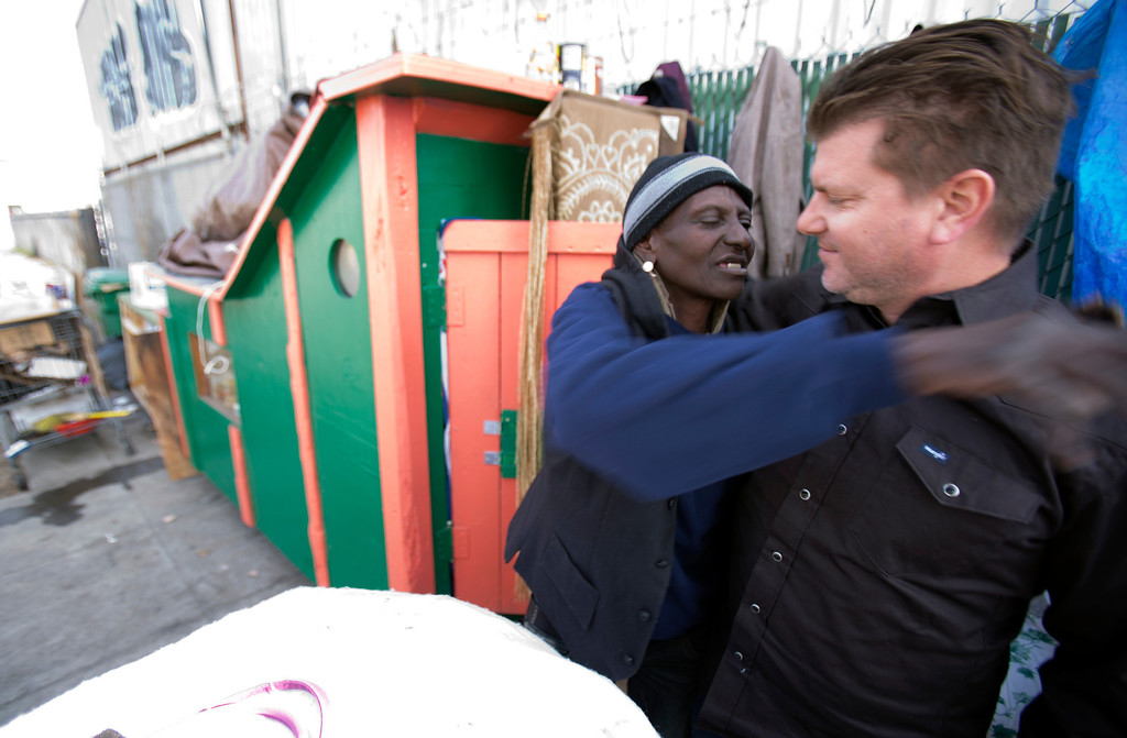 ". ""Wonder,\"" a homeless woman who now lives in on the street in west Oakland, Calif., hugs Greg Kloehn, a local man who takes discarded building materials and turns them into rolling shelters, Tuesday, Dec. 31, 2013. (D. Ross Cameron/Bay Area News Group)"