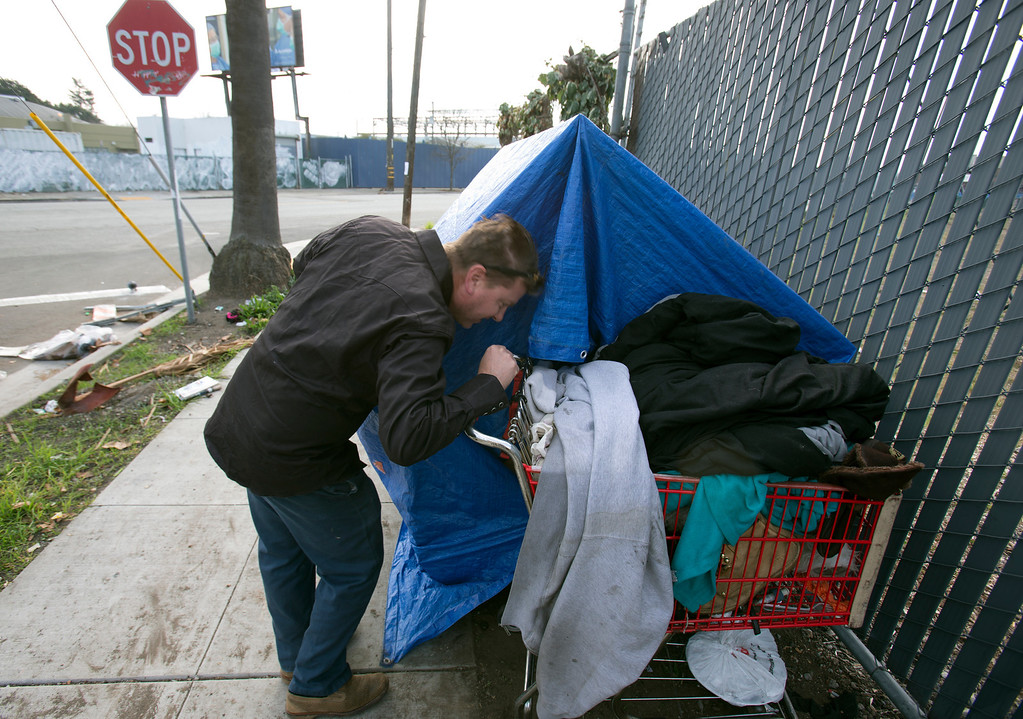 . Greg Kloehn, who takes discarded trash and turns it into rolling shelters for homeless people in his west Oakland, Calif. neighborhood, checks on the welfare of June, a homeless man who now lives in the shelter he built for him, alongside another built for June\'s wife, Tuesday, Dec. 31, 2013. (D. Ross Cameron/Bay Area News Group)