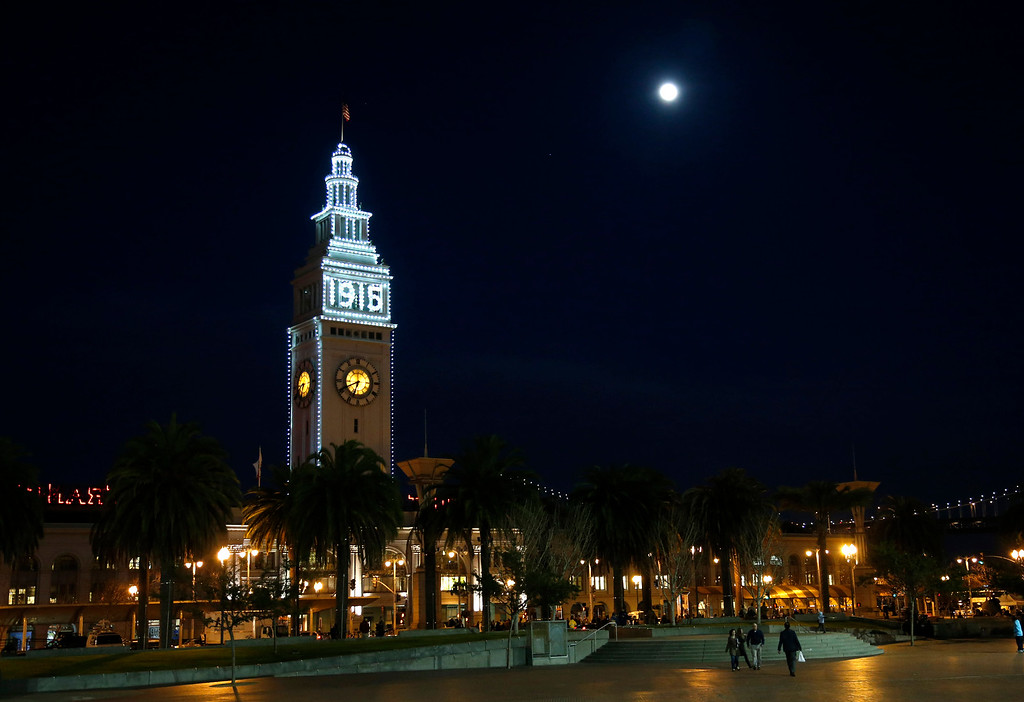 . The moon shines above the San Francisco Ferry Building following a ceremonial relighting of the iconic building Tuesday evening, March 3, 2015, as part of the 100th anniversary of the 1915 Panama-Pacific International Exposition. The lights will remain lit until Dec. 4, the night the original fair closed. (Karl Mondon/Bay Area News Group)