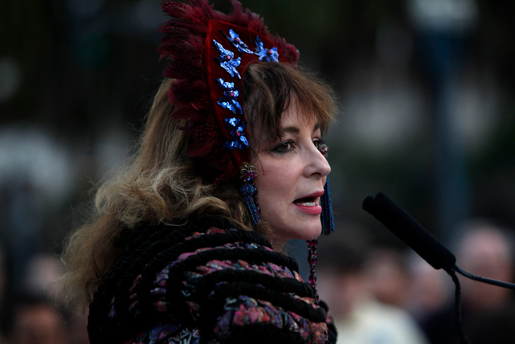 . Donna Ewald Huggins dresses in turn of the 20th Century clothing as she hosts the ceremonial relighting of the Ferry Building Tuesday evening, March 3, 2015, as part of the 100th anniversary of the 1915 Panama-Pacific International Exposition. Huggins\' grandparents met at the 1915 exhibition. (Karl Mondon/Bay Area News Group)
