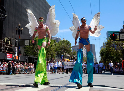 A couple winged stilt-walkers trek up Market Street in the SF Pride parade in San Francisco, Calif., on Sunday, June 26, 2016. (Karl Mondon/Bay Area News Group)