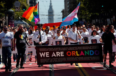 """We Are Orlando"" members carry pictures of those struck down by the Orlando nightclub massacre as they march in the SF Pride parade on Sunday, June 26, 2016, in San Francisco, Calif. (Karl Mondon/Bay Area News Group)"